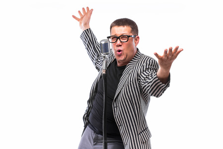 the showman: Portrait of middle age showman singing in microphone with emotional gesture