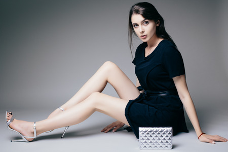 girl sitting down: Beauty brunette girl sitting down and possing on grey background. Fashion photo.