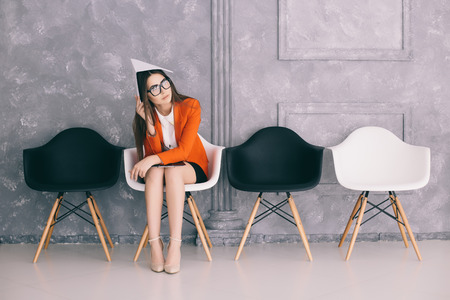 Bored young businesswoman holding paper and looking away while sitting on chair Stock fotó - 63672392