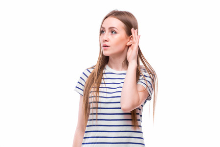 Young woman with a hearing disorder or hearing loss cupping her hand behind her ear with her head turned aside to try and amplify and channel the available sound to her ear drum Stock Photo