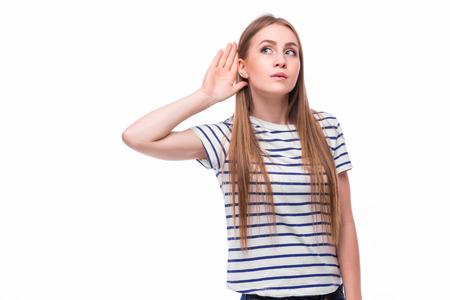 pelirrojas: Mujer joven con un trastorno de la audición o pérdida ahuecando la mano detrás de la oreja, con la cabeza oír apartó del camino para tratar de amplificar y canalizar el sonido disponible para su tímpano