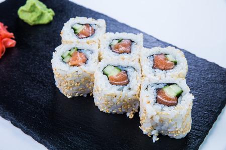 susi: Sushi Set nigiri and sushi rolls on black stone slate. Restaurant food concept.