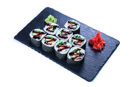 Sushi Set nigiri and sushi rolls on black stone slate. Restaurant food concept.