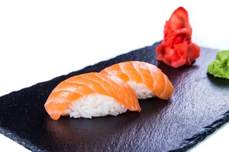 susi: Sushi Set and sushi rolls on black stone slate. Restaurant food concept. Stock Photo
