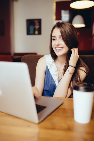 outdoor portrait of a young girl she works as a freelancer in a cafe drinking a delicious hot Cup of coffee from text send mail loads the photo freelancer Stock Photo
