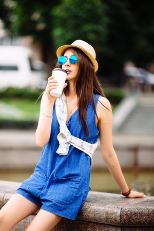 Nice beauty girl with take out coffee in city squar. Urban life concept.