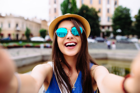 Young girl take selfie from hands with phone on summer city street. Urban life concept. Stockfoto
