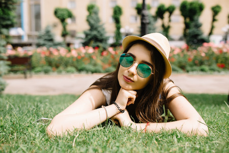 pensador: Young beautiful girl in hat lying on grass and looking happy Foto de archivo