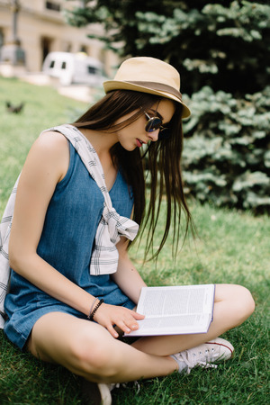 girl studying: young woman sitting on the grass and reading the book. Urban lifestyle concept.