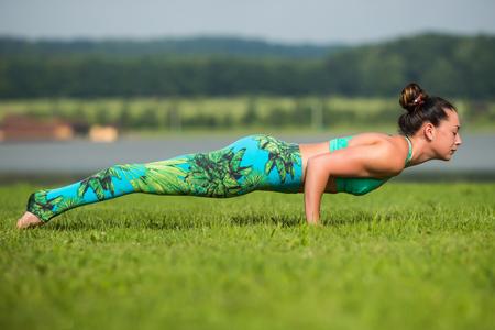 hasta: Plank.Yoga girl training outdoors on nature background. Yoga concept.