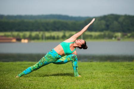 hasta: Parsvakonasana. Yoga girl training outdoors on nature background. Yoga concept.