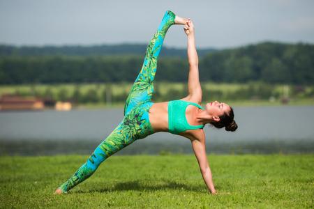 hasta: Vasisthasana. Yoga girl training outdoors on nature background. Yoga concept.