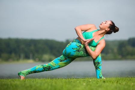 ushtrasana: parivritta parsvakonasana. Yoga girl training outdoors on nature background. Yoga concept.