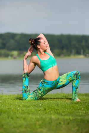 eka pada rajakapotasana. Yoga girl training outdoors on nature background. Yoga concept. Stock Photo