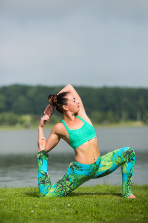 ushtrasana: eka pada rajakapotasana. Yoga girl training outdoors on nature background. Yoga concept. Stock Photo