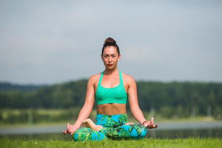 hasta: meditation. Yoga girl training outdoors on nature background. Yoga concept. Stock Photo