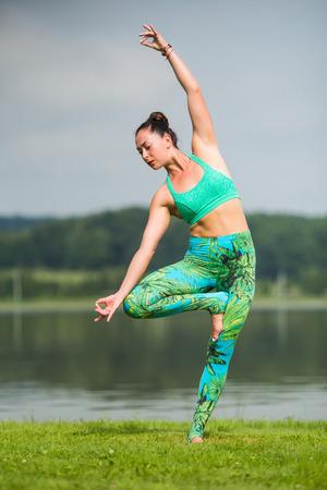 sukhasana: vrikshasana. Yoga girl training outdoors on nature background. Yoga concept. Stock Photo