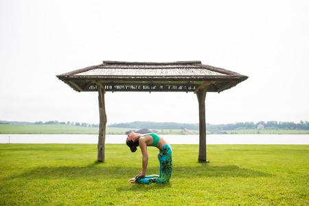 ushtrasana: ushtrasana. Yoga girl training outdoors on nature background. Yoga concept.
