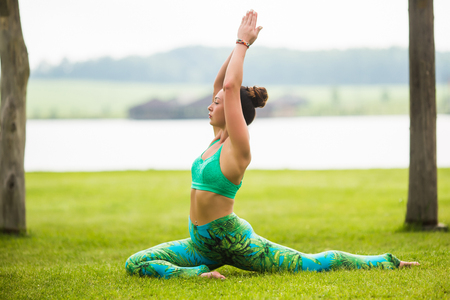 hasta: eka pada rajakapotasana. Yoga girl training outdoors on nature background. Yoga concept. Stock Photo