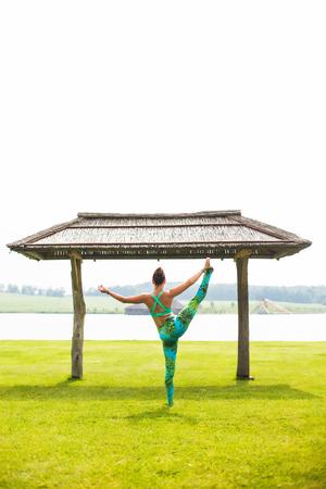 utthita: Yoga girl training outdoors on nature background. Yoga concept.