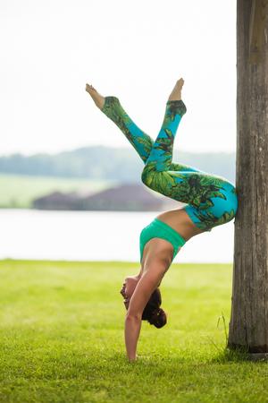 sukhasana: adho mukha vrikshasana. Yoga girl training outdoors on nature background. Yoga concept. Stock Photo