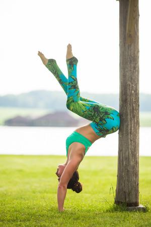 ushtrasana: adho mukha vrikshasana. Yoga girl training outdoors on nature background. Yoga concept. Stock Photo
