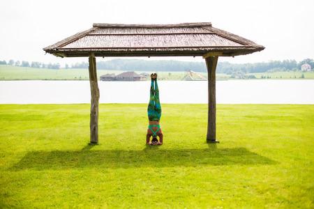 hasta: shirshasana. Yoga girl training outdoors on nature background. Yoga concept.