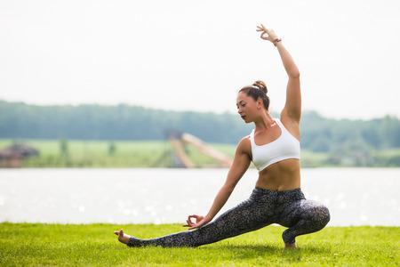 hasta: Yoga girl training outdoors on nature background. Yoga concept.