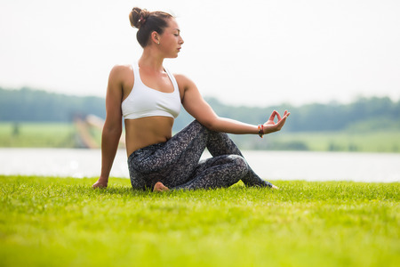 hasta: matsyendrasana. Yoga girl training outdoors on nature background. Yoga concept. Stock Photo