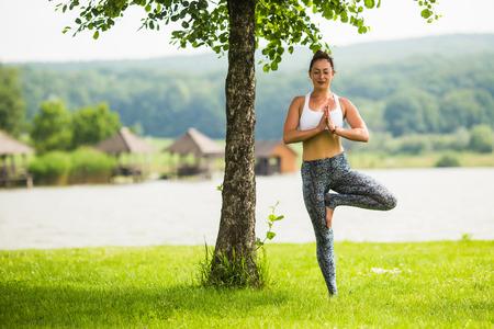 hasta: vrikshasana. Yoga girl training outdoors on nature background. Yoga concept. Stock Photo