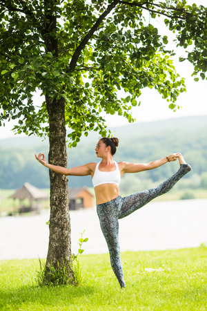 hasta: utthita hasta padangusthasana. Yoga girl training outdoors on nature background. Yoga concept. Stock Photo