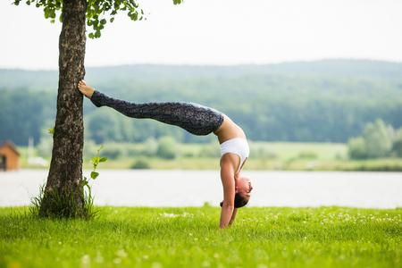 hasta: adho mukha vrikshasana. Yoga girl training outdoors on nature background. Yoga concept. Stock Photo