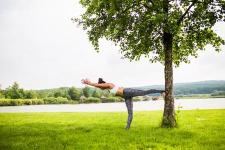 virabhadrasana. Yoga girl training outdoors on nature background. Yoga concept. Stock Photo