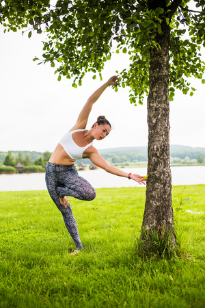 vrikshasana. Yoga girl training outdoors on nature background. Yoga concept. Stock Photo
