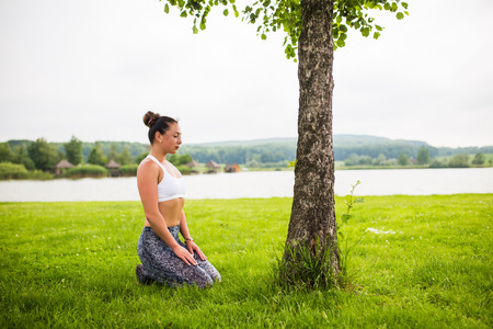 virasana. Yoga girl training outdoors on nature background. Yoga concept.