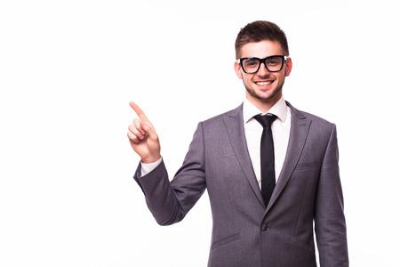Handsome smiling businessman pointing finger away over gray background