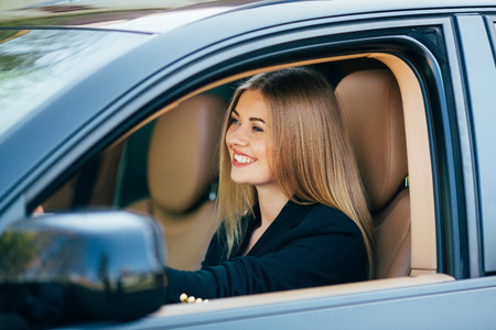 Attractive business woman with sunglasses smiling and driving her car. Stock Photo