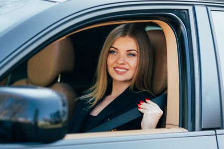 fastens: Beautiful young happy woman fastens a seat belt in the car Stock Photo