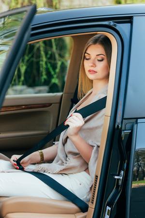 cinturón de seguridad: Mujer acústico de cinturones en un coche Foto de archivo