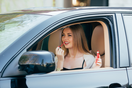 applying lipstick: Cute  girl applying lipstick in a car Stock Photo