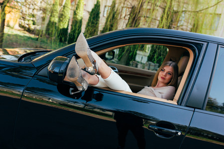 expensive car: Girl in expensive car with legs on window