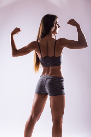 showing muscles: Athletic young woman showing muscles of the back and hands
