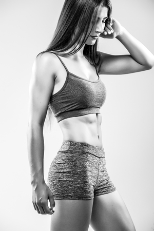Athletic young woman showing muscles of  hands. Black and white. Stock Photo