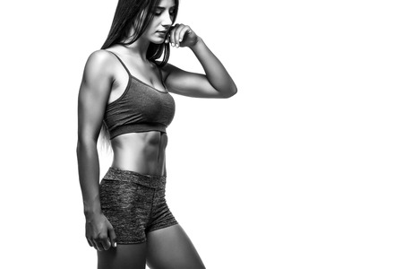 showing muscles: Athletic young woman showing muscles of  hands. Black and white. Stock Photo