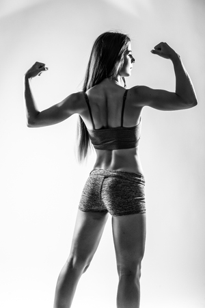 showing muscles: Athletic young woman showing muscles of the back and hands. Black and white.