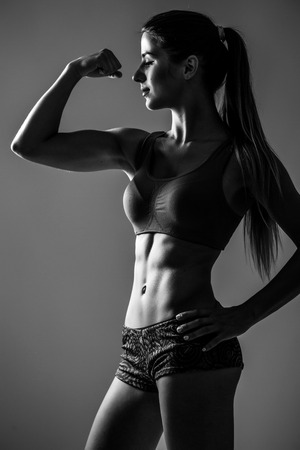 showing muscles: Athletic young woman showing muscles  hands Stock Photo