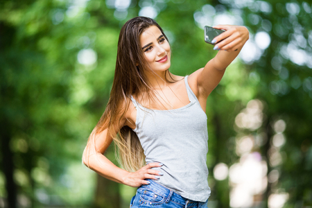Outdoor portrait of beautiful girl taking a selfie with mobile phone in city park.
