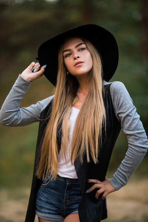 Autumnal happiness idea. Happy cheerful young woman in black hat outdoor. Joyful attractive girl  in park. Stock Photo