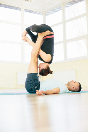 ushtrasana: Atractive yoga couple , man and woman, practice exercises in a training hall background. Yoga concept.