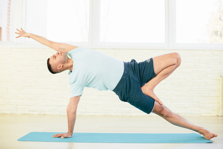 hasta: Handsome yoga man practice in a training hall background. Yoga concept.